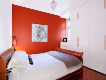 Modern bedroom design idea with floorboards & built-in wardrobe using orange colours - Bedroom photo 524617