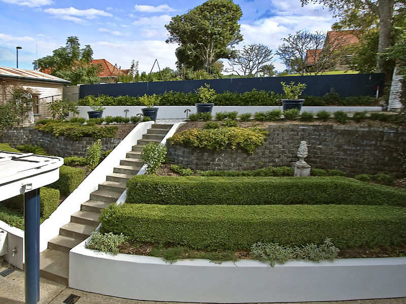 garden design using bluestone with retaining wall hedging