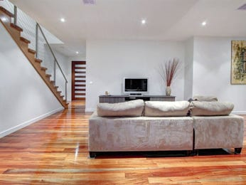 Open plan living room using grey colours with floorboards & staircase - Living Area photo 1257815