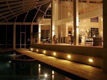 Indoor-outdoor outdoor living design with glass balustrade & ground lighting using brick - Outdoor Living Photo 404673