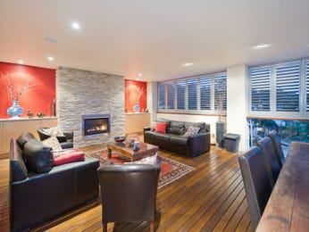 Open plan living room using black colours with stone & fireplace - Living Area photo 1516630