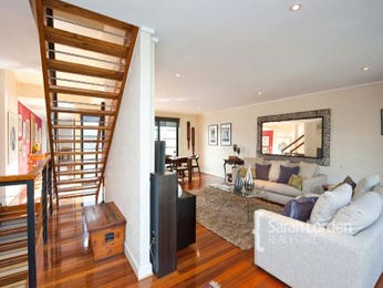 Open plan living room using brown colours with carpet & staircase - Living Area photo 160814