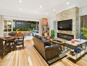 Dining-living living room using brown colours with floorboards & fireplace - Living Area photo 16732357