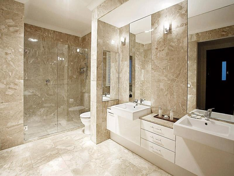 Modern bathroom design with twin basins using frameless for Latest bathroom tiles design
