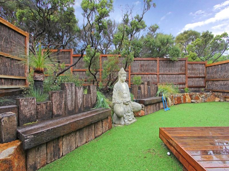 Landscaped garden design using grass with deck sculpture for Back garden designs australia