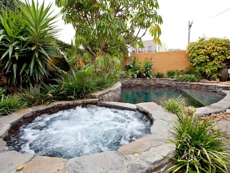 Landscaped garden design using pebbles with pool for Garden designs using pebbles